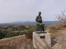 二の丸跡の滝廉太郎像と九重の山並…