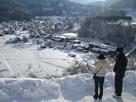 雪の合掌造集落を望む